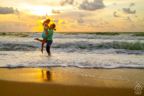 Fort Lauderdale Beach Portrait Session for Engagement - He lifts her up as they enjoy the sunrise on the beach.