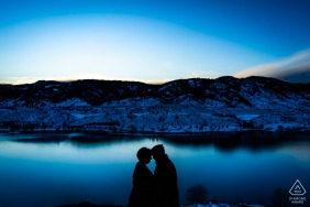 A couple shares an intimate moment while trying to stay warm as the sunsets during their winter engagement session in the foothills of Fort Collins, Colorado.