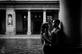 A couple during an engagement shoot under the corridor of the Uffizi Gallery in Florence