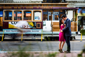 San Francisco	engagement photo session | A hug in front of a passing cable car