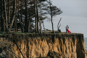 Moss Beach, California engagement portrait with a red dress flowing near the cliffs