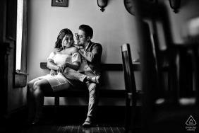 Prewed portrait de couple assis dans la lumière de la fenêtre au Black Lab Pub