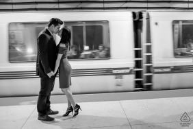Kiss on the Bart platform in San Francisco of a couple during an engagement photo session
