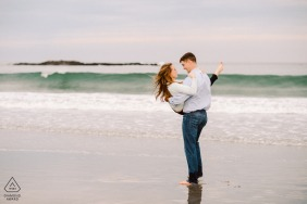 A couple enjoying the seaside beach in York Harbor Beach, Maine during an engagement photography session