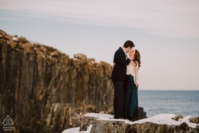 A couple enbracing each other by the coastal rocky shore at the Cliff House, Cape Neddick, Maine