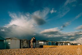 Couple walking along beach huts under dramatic stormy skies at Shoreham Beach, West Sussex, UK
