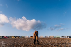 Romantic image of couple with blue skies and colourful beach huts at Shoreham Beach, West Sussex, UK
