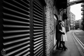 Black and White image of Couple in striking architecture in Shad Thames, London, UK