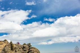 O casal de noivos se ajuda sobre o terreno rochoso do penhasco em Juniper Pass, Colorado