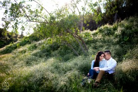 Los Angeles couple sitting in tall grass for their engagement portraits