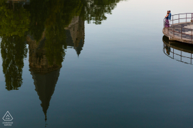 a Couple standing on footbridge and a monument reflection in the river in Metz, France