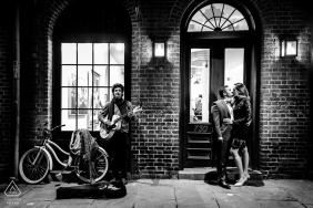 new orleans couple pose on the steps of a business as a street musician plays for them