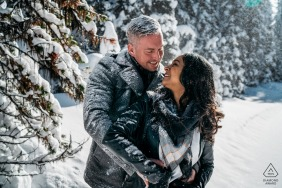 a young Couple having fun during the winter engagement session in the snow and trees of Lake Louise, Banff National Park, AB, Canada