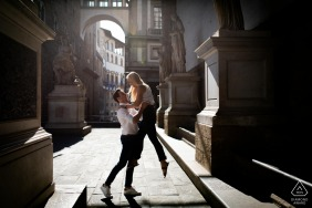He is making her fly during an afternoon portrait shoot in Loggia dei Lanzi in florence