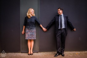 Paris couple holding hands against a wall during their engagement portrait session
