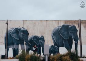 Neuseeland-Paar vor Straßenkunstmalerei von Elefanten in Christchurch