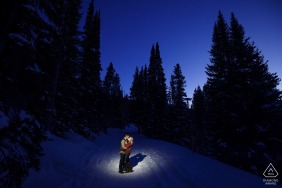 A couple share a kiss along snowy Boreas Pass Road in Breckenridge at twilight during a winter engagement session