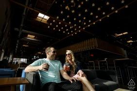 Le jeune couple partage un verre à Improper City à Denver lors de leurs photos de fiançailles