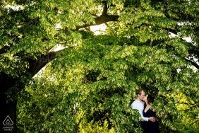 pareja comprometida posan para retratos ocultos en las hojas de Rosice