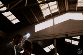 The couple exchanges a genuine look, while under a very slight ray of light in an Abandoned garage in Leiria, Portugal