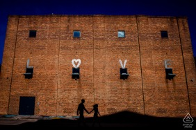 Baltimore, Maryland engaged couple holding hands and walking under the word Love, spelled out on a brick building