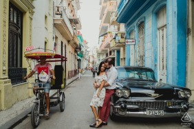 A couple leaning on a car in the streets of Cuba during a prewedding engagement shoot