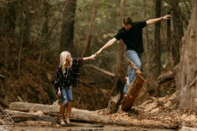 a Couple playing in the woods during engagement photography session Near Columbia, Mississippi