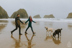 an engaged Couple walking their dogs on a rainy beach of Ecola State Park for a portrait shoot