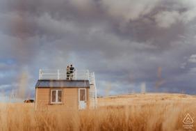 Godley Head Couple steht auf dem Dach einer alten antarktischen Hütte während ihres Fotoshootings in Christchurch, Neuseeland