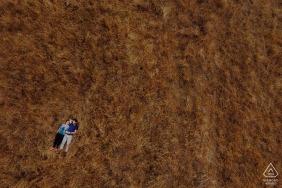Godley Head, Christchurch NZ engagement drone portrait d'un couple allongé dans l'herbe