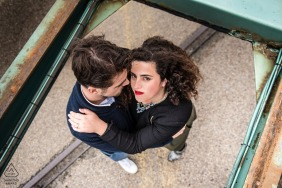A couple, top view, the girl has a strong look and a red lipstick in this Le Havre, France engagement portrait