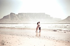 engagement portrait of The couple kissing in front of one of the 7 natural wonders of the world at Blouberg Beach