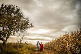 casal de noivos caminha atrás de um retrato No meio da estrada, perto do milharal queimado e da tempestade que se aproxima em Pirinópolis, Goiás