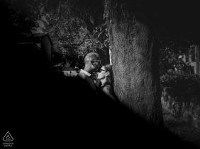 Séance photo de fiançailles amoureuse de Sarazana en noir et blanc près d'un grand arbre