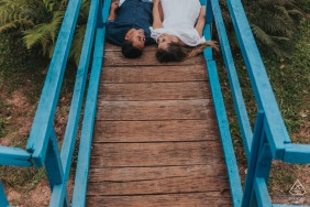 Caeté MG couple portraits while lying down on a wooden boardwalk