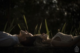 Couple lie on their backs looking up during an engagement shoot in Parque das Ruínas, Santa Teresa, Rio de Janeiro, Brazil