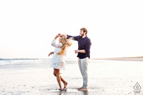 Avalon, New Jersey beach engagement session with a couple spinning and dancing by the water's edge at the beach