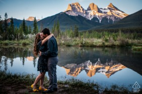 a Canmore, AB, Canada Sunrise kiss for this engagement portrait by the water with reflections