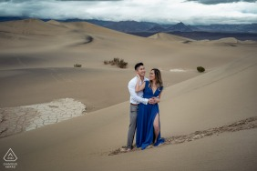 A Happy couple posing for engagement portraits in the sand dunes of Death Valley National Park, CA, USA