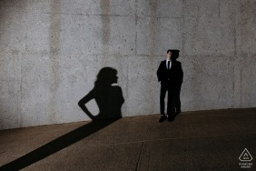 Cape Town couple pose for an engagement portrait against a concrete wall, with the woman shadowed on the wall