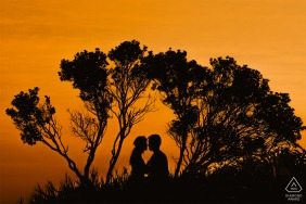 Aracruz, Espírito Santo, Brazil engagement image with an orange sunset sky and a silhouetted couple