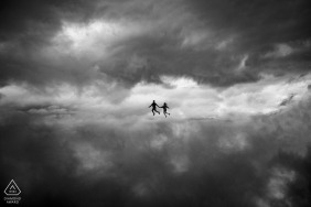 Pre-Wed Photo in Da Lat of couple walking amongst the clouds in the sky