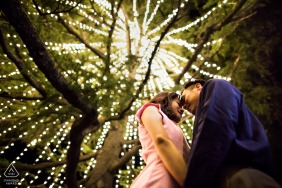 Los Gatos Love under Christmas tree lights during engagement photo session