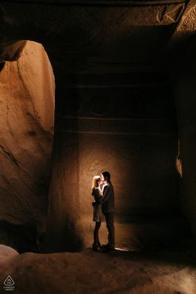 Sessão de noivado na Capadócia de um retrato iluminado de um casal em uma caverna