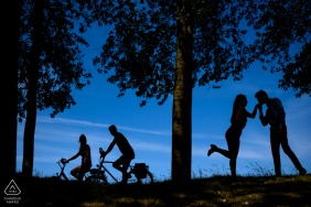 A silhouette portrait of a couple with a bicycling couple riding by in De Klinge