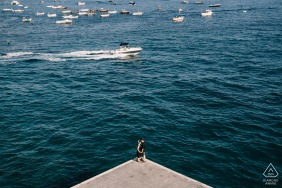 A couple standing on the corner of a dock out on the water with boats floating in Positano