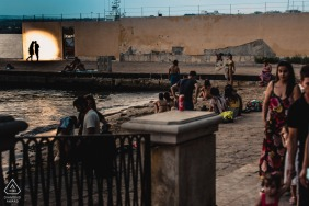 A couple lit and silhouetted beyond a scene of beachgoers at Ortigia Island, Sicily