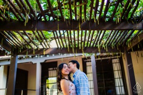 A kiss under the trellis during engagement shoot in Los Gatos