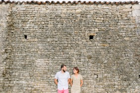 Vendée, France Loving couple laughing and leaning against a wall in the french countryside