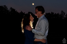 Backlit couple portrait standing in front of the full moon in Heather near Eindhoven